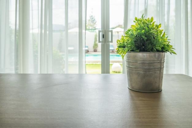 Mesa de madera con planta jarrón vintage en cortina