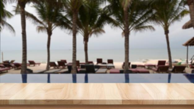 Mesa de madera y playa de verano borrosa.