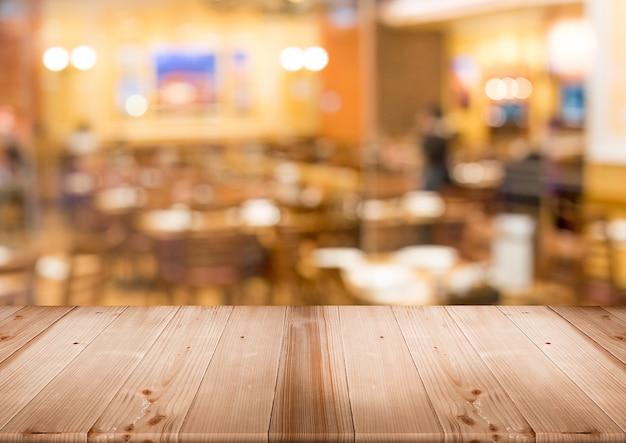 Mesa de madera para productos de pantalla con restaurante borroso