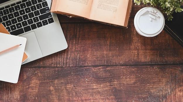 Mesa de madera que incluye libro, lápiz, taza de café, planta en maceta, computadora portátil y cuaderno.
