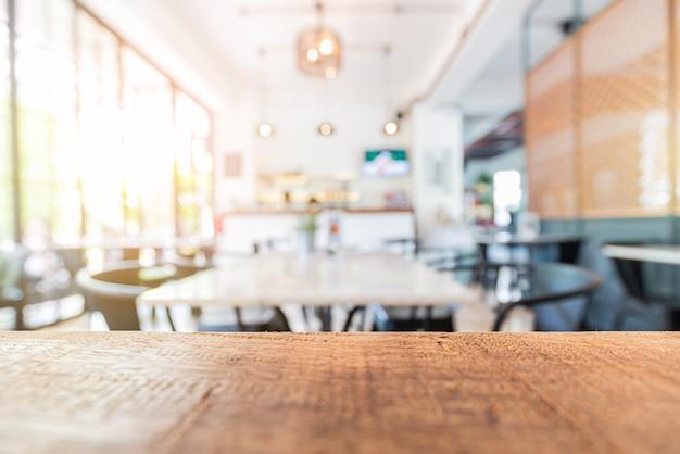Mesa de madera en restaurante y decoración interior borrosa.