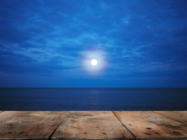 Mesa de madera sobre la playa de verano en la noche con luna llena