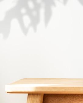 Mesa de madera con sombra vegetal en una pared.