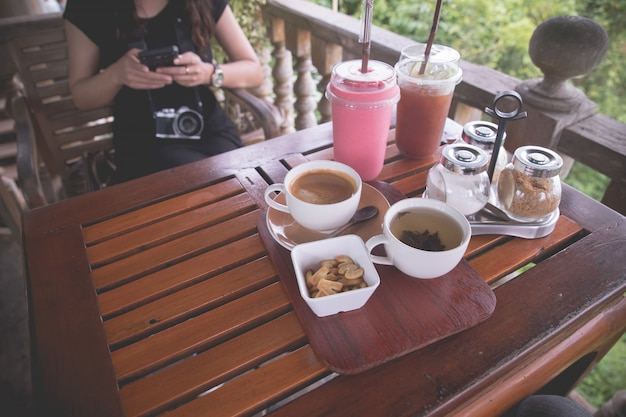 Mesa de madera con taza de café negro y batido de fresa fría.