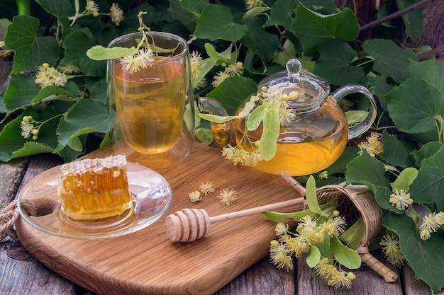 En una mesa de madera, té de limón en un vaso transparente, una tetera con té y miel.