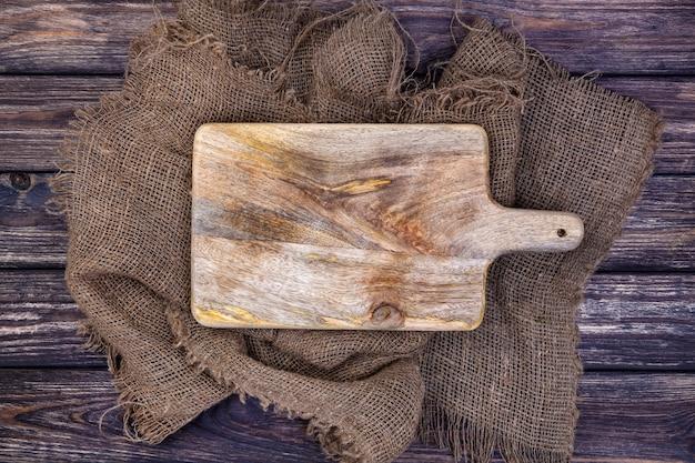 Mesa de madera con tela de arpillera y tabla de cortar.
