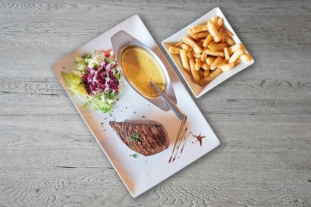Mesa de madera texturizada y plato con bistec a la parrilla.