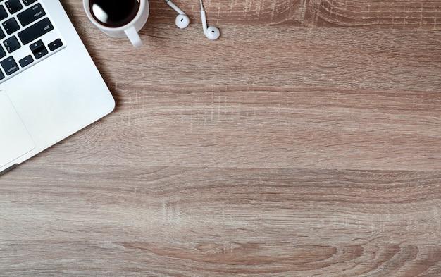 Mesa de madera de trabajo con computadora portátil y taza de café