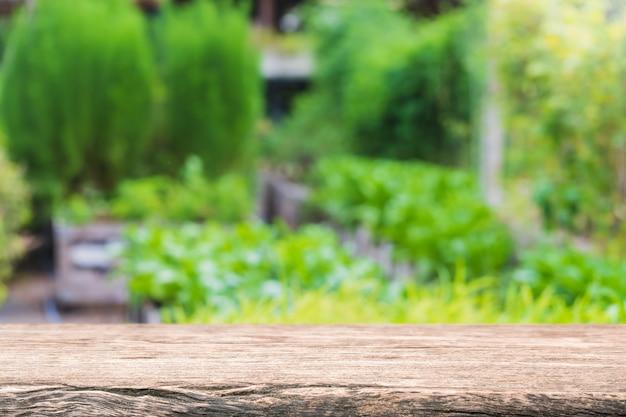 Mesa de madera vacía y árbol verde borroso y vegetales en granjas agrícolas. antecedentes.
