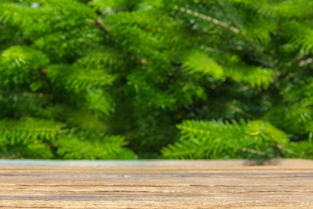 Mesa de madera vacía en una de árboles verdes, un espacio con el área de montaje