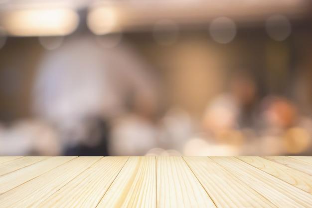 Mesa de madera vacía con chef cocinando en cocina de restaurante abstracto fondo desenfocado borroso