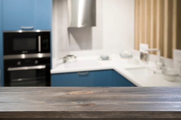 Mesa de madera vacía y cocina moderna azul desenfocada para diseñar y exhibir sus productos. fondo de cocina abstracto borroso.