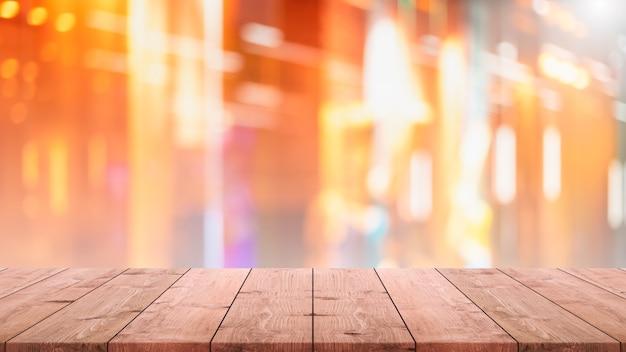 Mesa de madera vacía y desenfoque de la ventana de cristal interior restaurante y cafetería banner simulan el fondo.