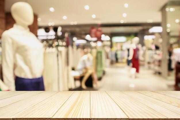 Mesa de madera vacía con escaparate de tienda de ropa boutique de moda de mujer en centro comercial