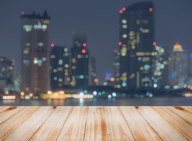 Mesa de madera vacía con fondo borroso del horizonte de la ciudad por la noche