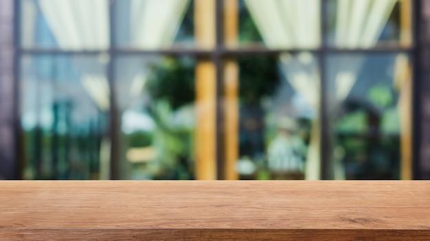 Mesa de madera vacía y fondo interior borroso de cafetería y restaurante.