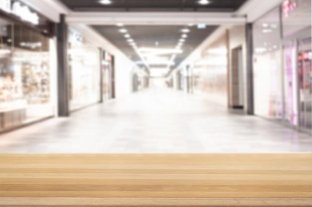 Mesa de madera vacía y fondo interior de grandes almacenes, exhibición del producto, fondo interior claro borroso con grandes almacenes bokeh, listo para el montaje del producto.
