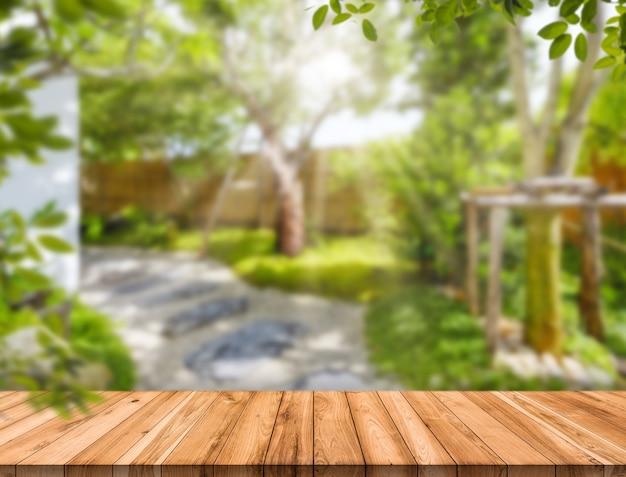 Mesa de madera vacía en el jardín de desenfoque