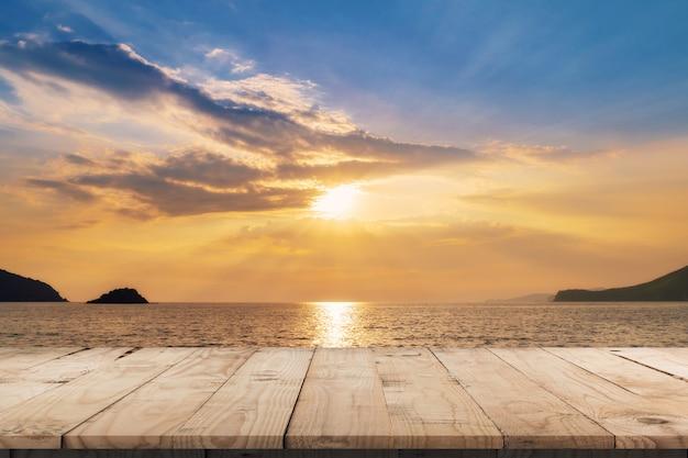 Mesa de madera vacía y paisaje de puesta de sol en el mar de la costa, olas con montaje de pantalla