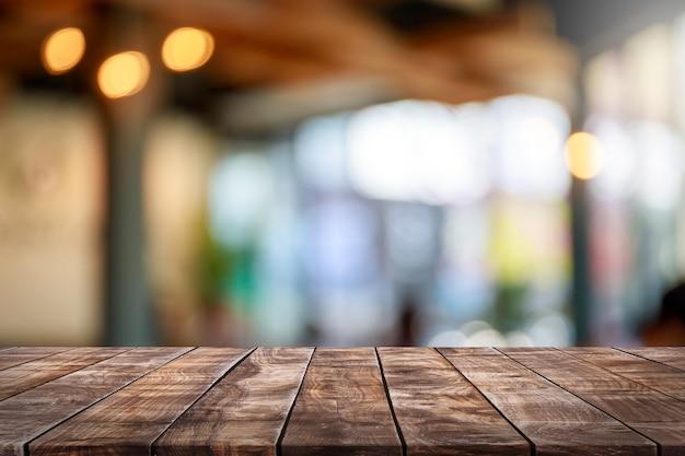 La mesa de madera vacía y la pancarta interior del restaurante de la ventana de cristal borrosa se burlan del fondo abstracto - se pueden utilizar para exhibir o montar sus productos
