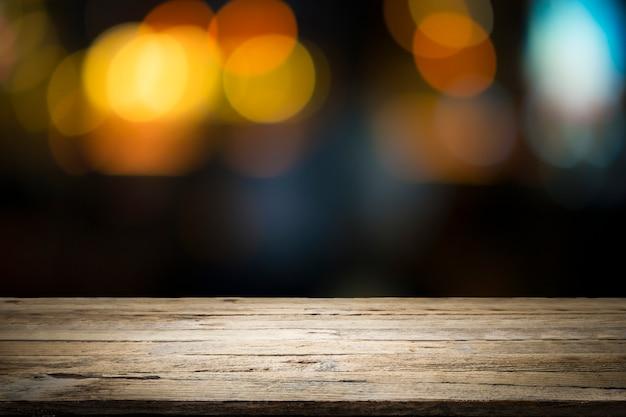 Mesa de madera vacía de plataforma y bokeh por la noche.