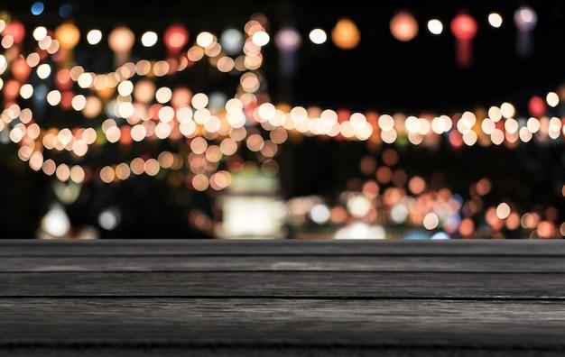 Mesa de madera vacía selectiva delante de fondo claro festivo borroso abstracto con puntos de luz y bokeh
