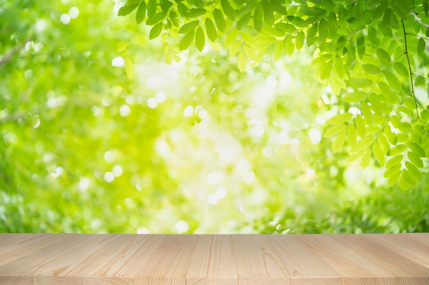 Mesa de madera vacía sobre fondo verde de la naturaleza con bokeh de belleza bajo la luz solar.