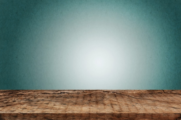 Mesa de madera vacía sobre pared verde oscuro
