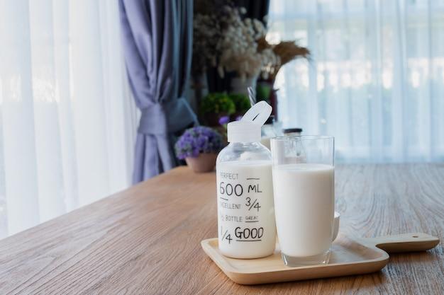 Mesa de madera con vaso de leche, leche de botella y despertador retro en la sala.