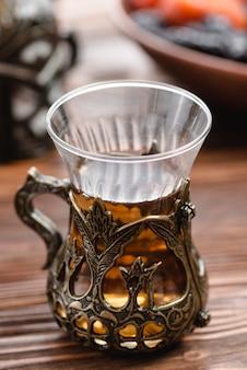 Mesa de madera de un vaso de té árabe turco tradicional