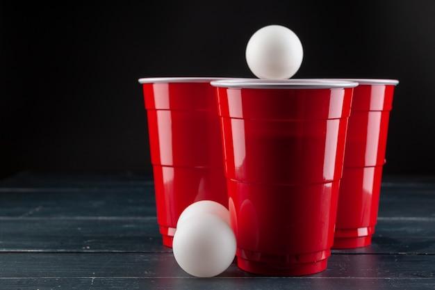 Mesa de madera con vasos rojos y bola para cerveza pong