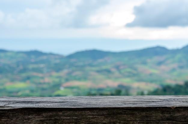 Mesa de madera vieja y vista a la montaña de desenfoque