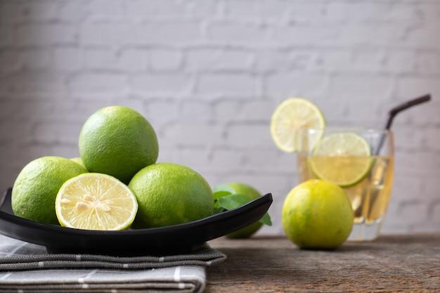 Mesa de madera con zumo de limón recién exprimido y rodajas de limón.