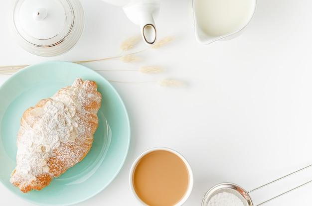 Mesa de la mañana. cruasanes recién hechos en platos turquesas, leche y café. de arriba hacia abajo, copie el espacio.