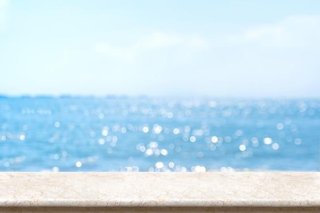 Mesa de mármol blanco con mar de bokeh borroso y cielo azul