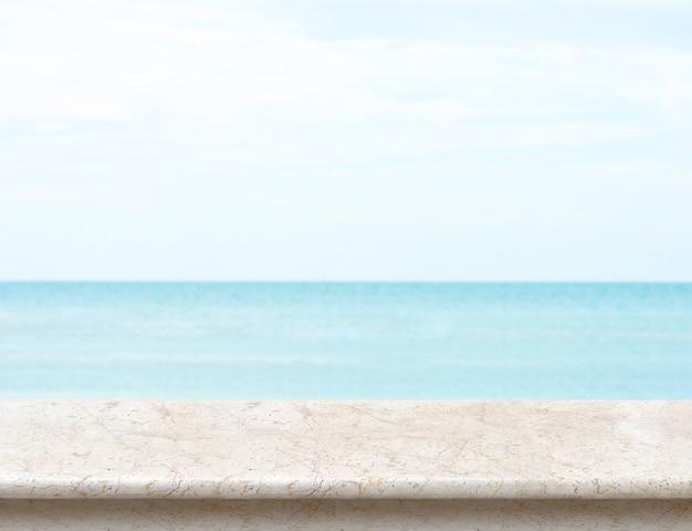 Mesa de mármol blanco con mar borrosa y cielo azul en el fondo