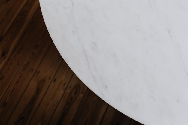 Mesa de mármol blanco y suelo de madera.