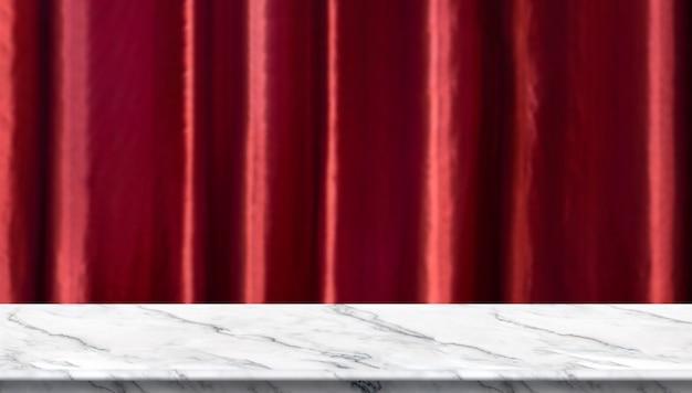 Mesa de mármol blanco vacío y fondo de cortina de lujo rojo vívido borroso