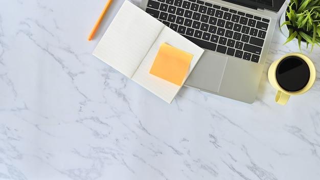 Mesa de mármol de escritorio de oficina con laptop, papel de cuaderno, lápiz y taza de café. por encima de la mesa de tiro.
