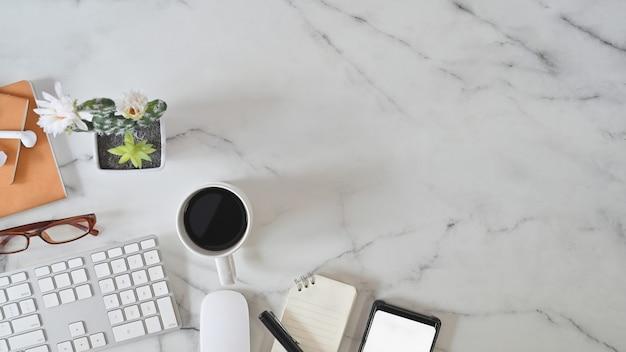 Mesa de mármol de escritorio de oficina con teclado de computadora, papel de cuaderno, bolígrafo y taza de café. por encima de la mesa de tiro.
