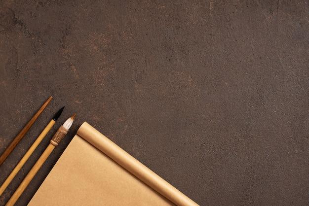Mesa marrón con cuaderno de dibujo artesanal y pinceles