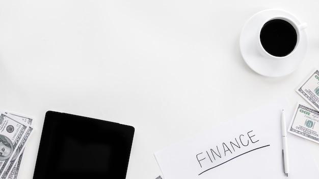 Mesa con material de trabajo de finanzas. café, dinero, tableta, bolígrafo, papeles