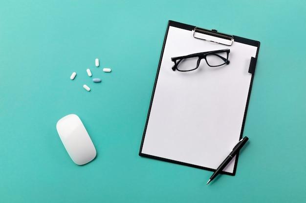 Mesa de médicos con tableta, bolígrafo, mouse y pastillas.