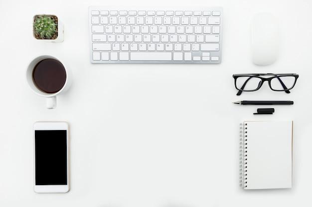 Mesa moderna de oficina blanca con aparatos de computadora y suministros en plano.