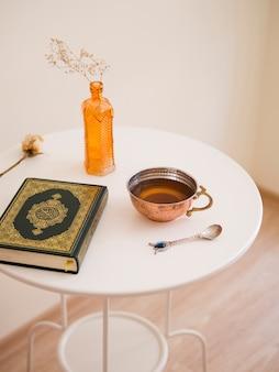 Mesa moderna con quran y taza de té.