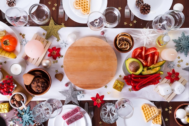 Mesa navideña con comida en un plato y decoración en mesa de madera oscura, endecha plana