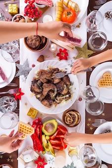 Mesa navideña con comida en un plato, manos de mamá y niño entregando comida y decoración en mesa de madera oscura, plano