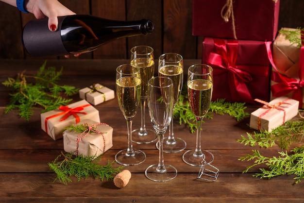 Mesa navideña con copas y una botella de vino de champagne