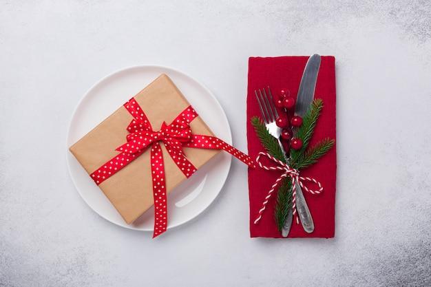 Mesa navideña con plato blanco, caja de regalo y cubiertos sobre fondo de piedra