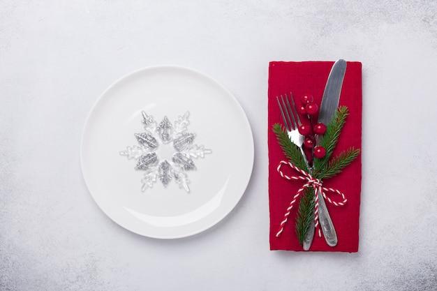 Mesa navideña con plato blanco, copos de nieve decorativos y cubiertos sobre fondo de piedra